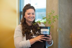 student holding plant from internship